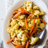 Up close overhead photo of roasted cauliflower and carrots on a white oval dish with a spoon
