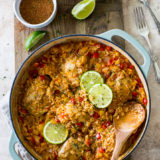 Overhead photo of one pot salsa chicken and rice dinner in a round baking dish surrounded by limes and spices