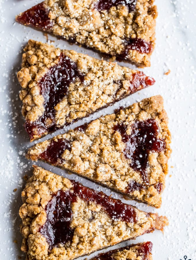 Wedges of jam crumb cookies in a row of six cookies on a light surface