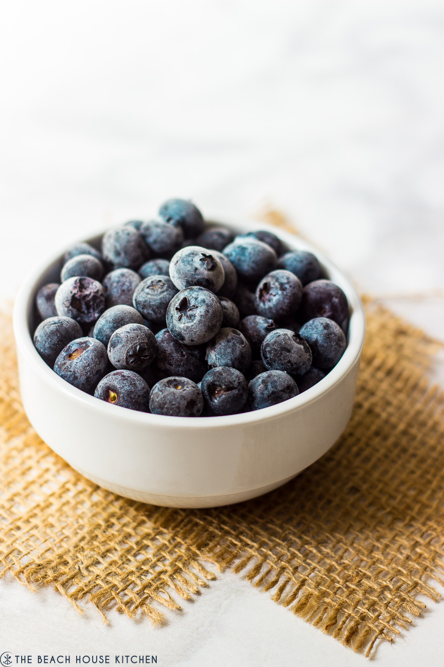 A white bowl filled with blueberries on two pieces of burlap