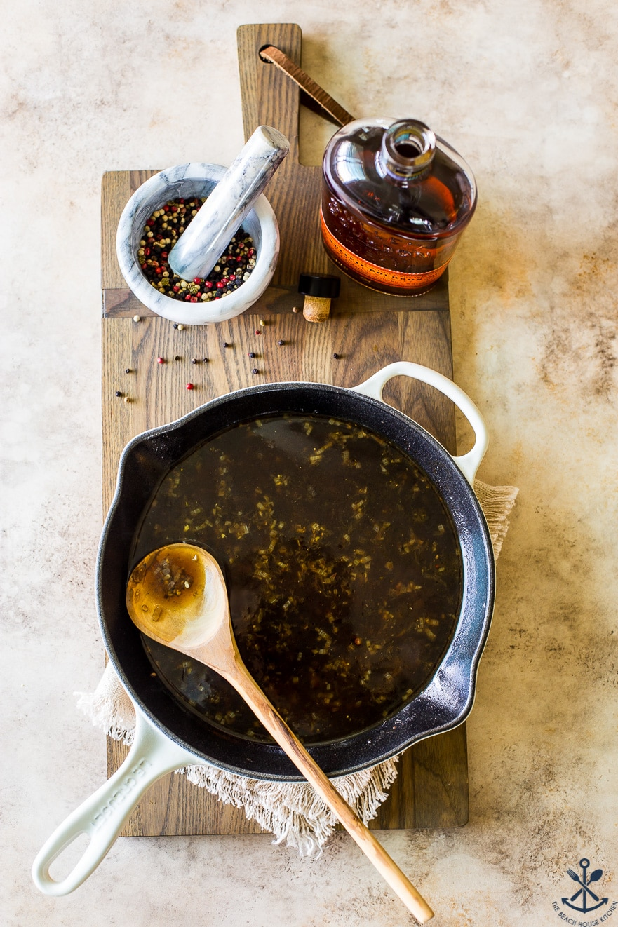 Overhead photo of beef broth in skillet with a wooden spoon