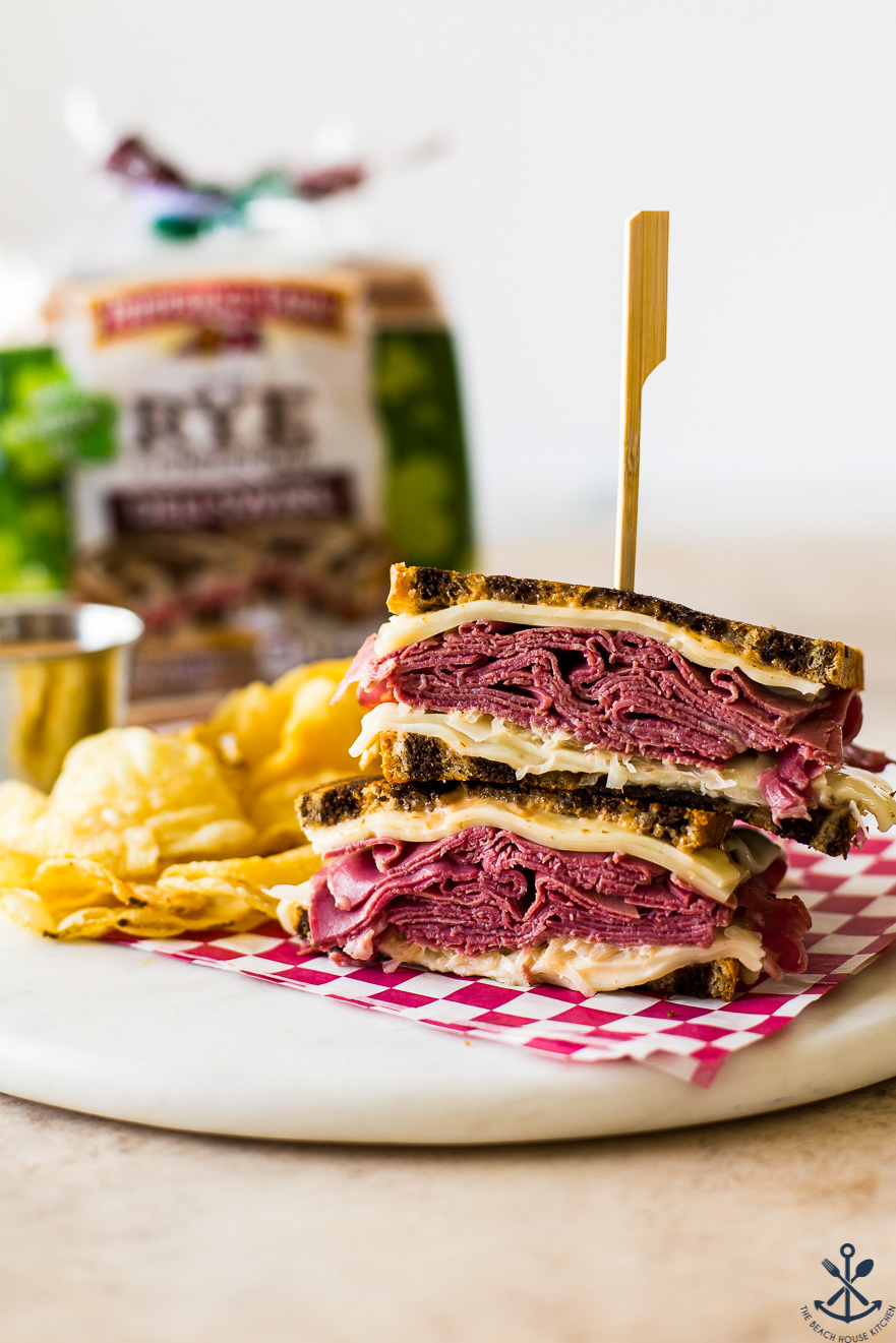 Classic Reuben Sandwich with chips and a loaf of rye bread in the background