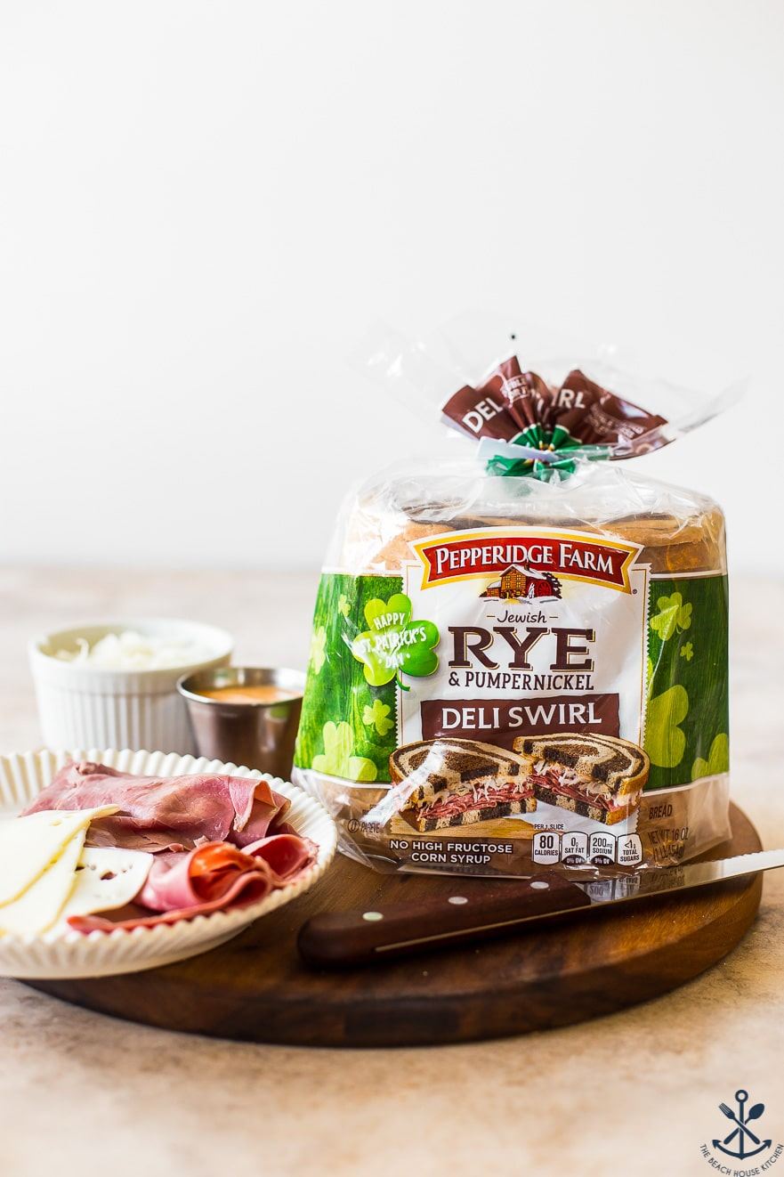 A bag of rye bread with a sharp knife and a plate of corned beef and Swiss cheese on a round wooden board