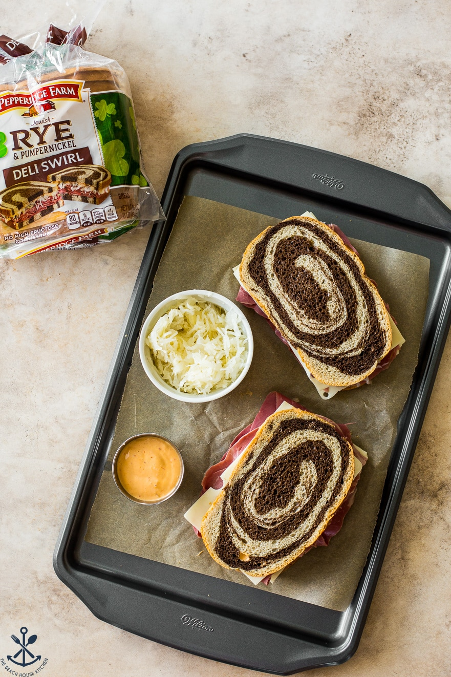 Overhead photo of two reuben sandwiches on a baking sheet with a bowl of sauerkraut and Russian dressing