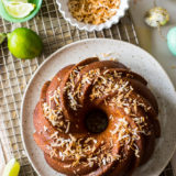 Overhead photo of key lime coconut bundt cake on a gold wire rack with a bowl of toasted coconut