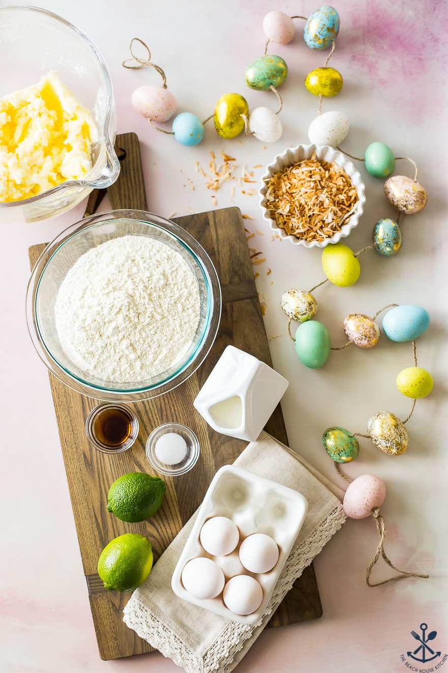 Overhead photo of ingredients for bundt cake in bowls on a wooden board with easter eggs off to the right side