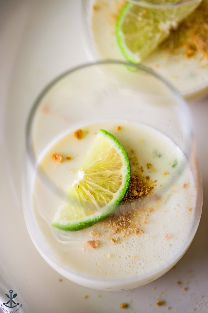 Up close photo of a glass filled with panna cotta, a lime slice and graham cracker crumbs