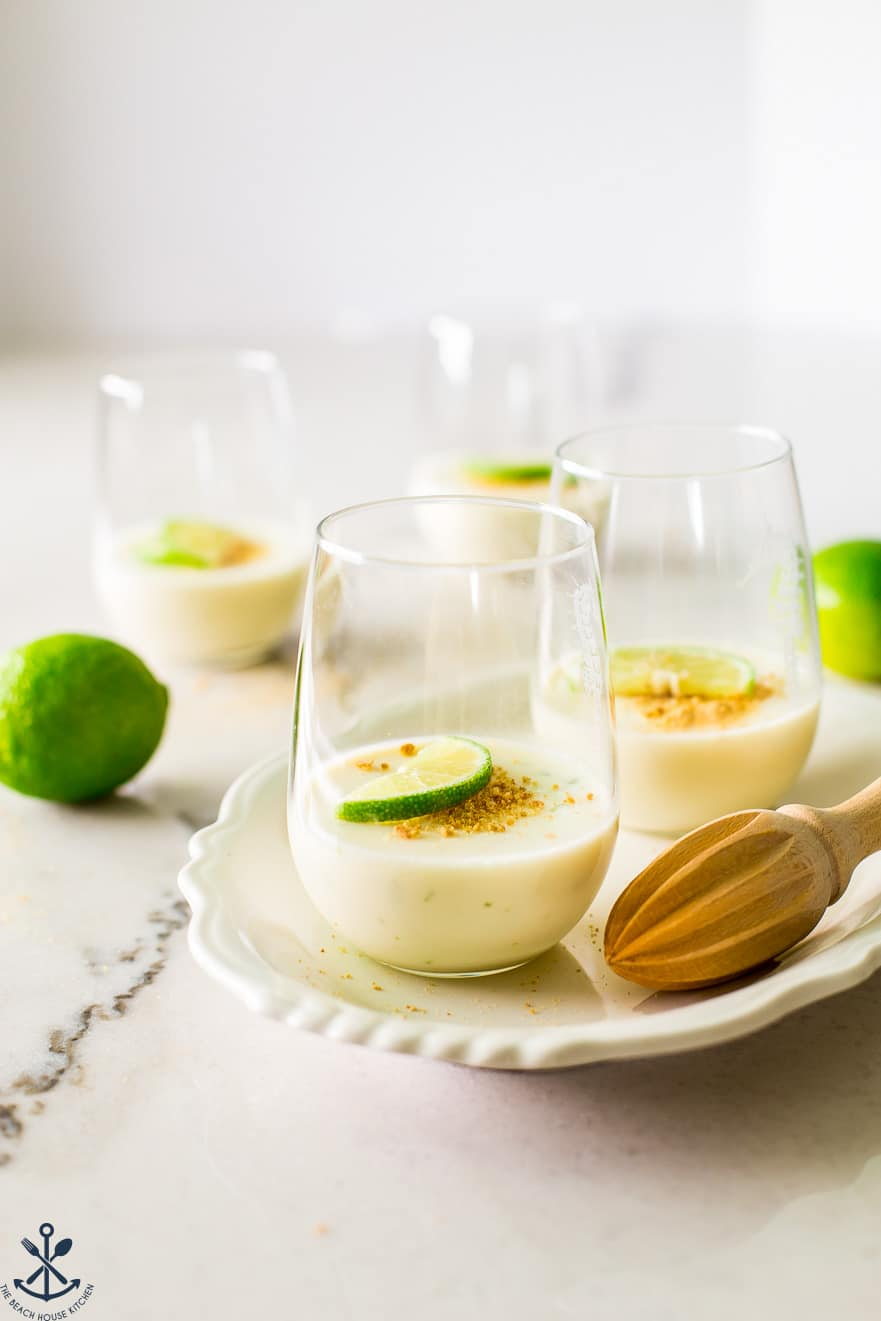 Glasses of key lime panna cotta on a white oval plate with a wooden juicer