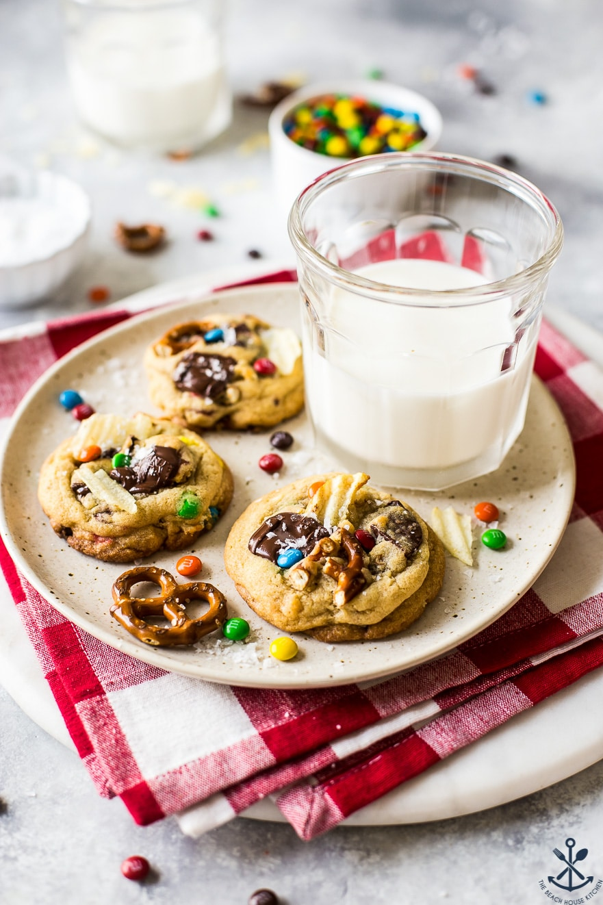 Three kitchen sink cookies on a plate with a glass of milk on a red check napkin