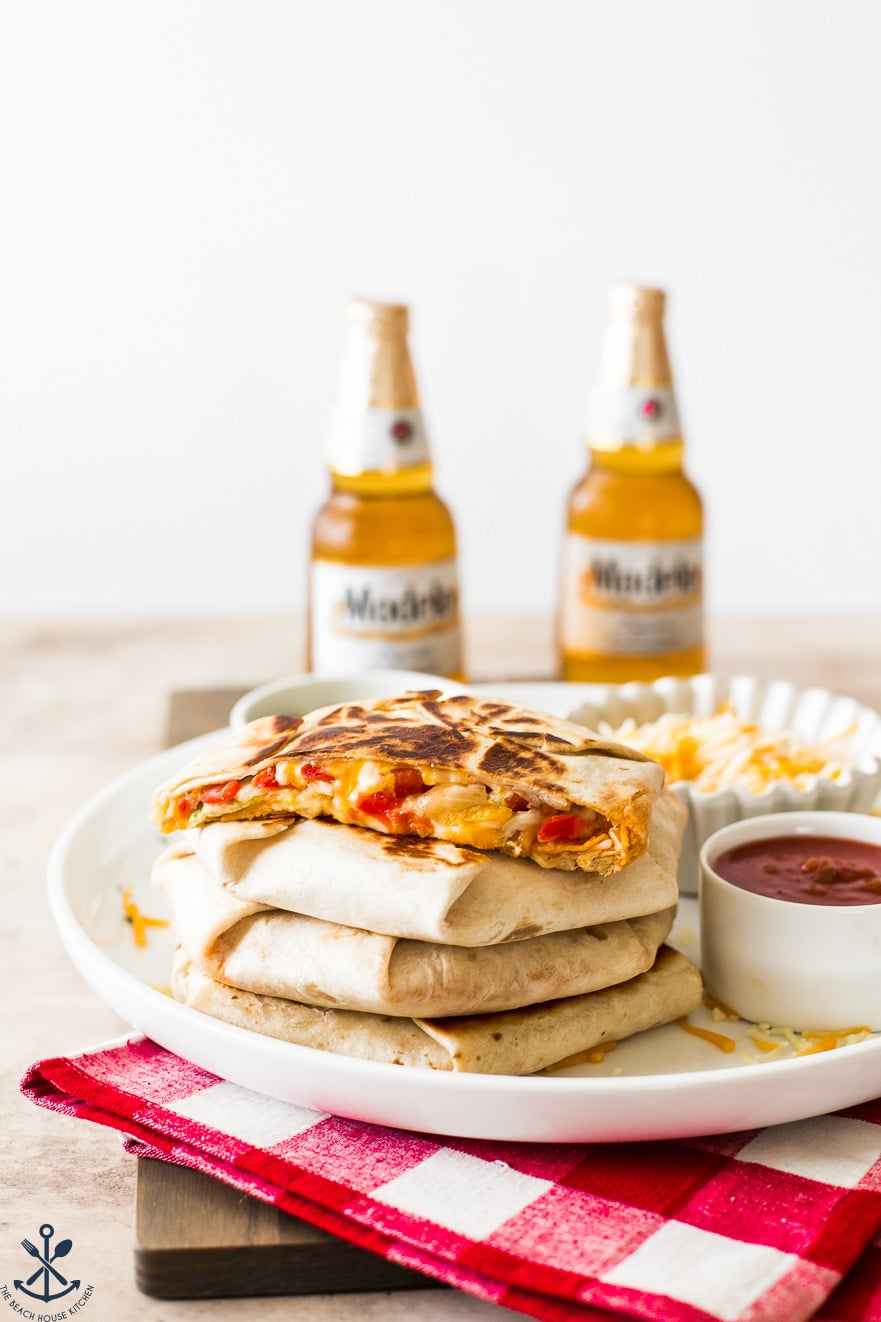 Stack of Buffalo Chicken Crunchwrap Supremes on a white platter with beers in background
