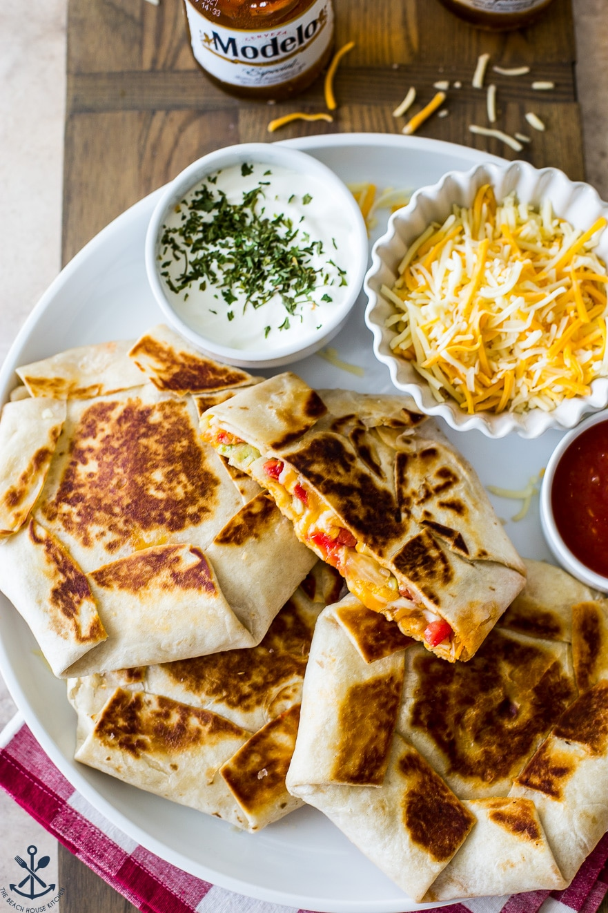 Overhead photo of buffalo chicken crunchwrap supremes on a white platter with shredded cheese and sour cream
