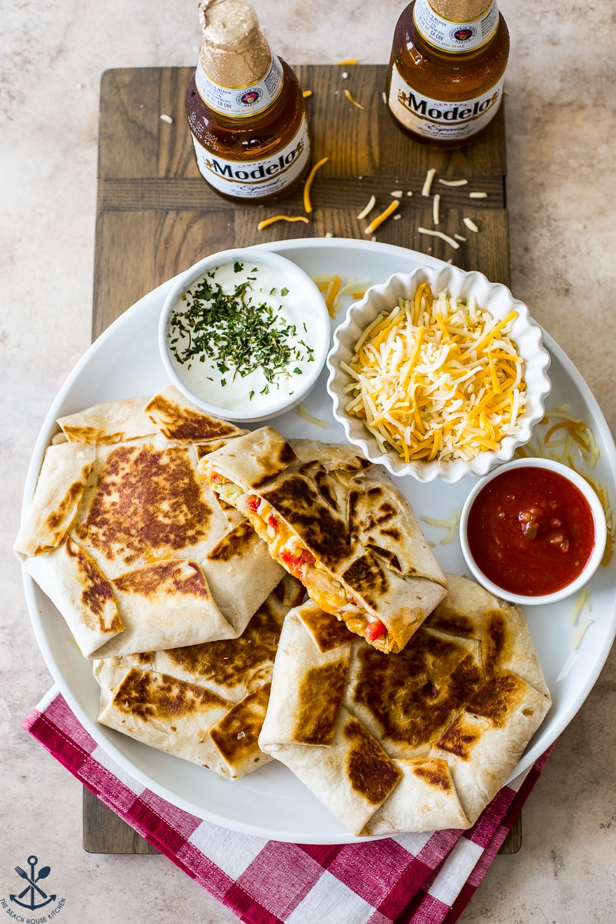 Overhead photo of buffalo chicken crunchwrap supremes on a white platerr with sour cream, shredded cheese and salsa