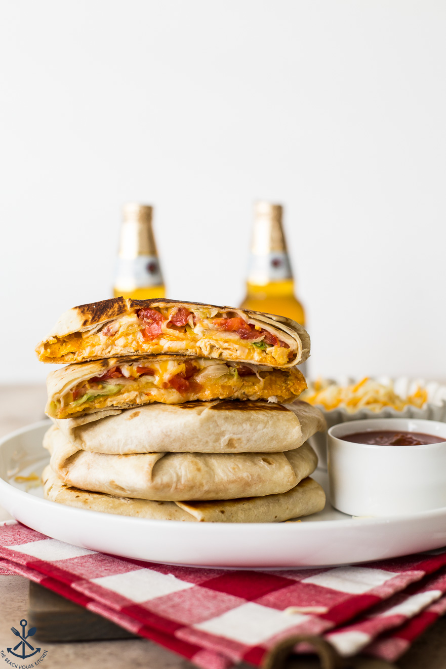 A stack of buffalo chicken crunchwrap supremes with beers in the background