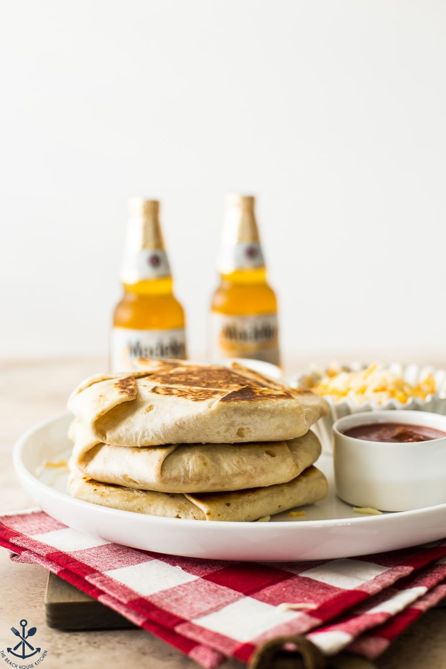 Stack of crunchwraps on a white platter with two beers in the background