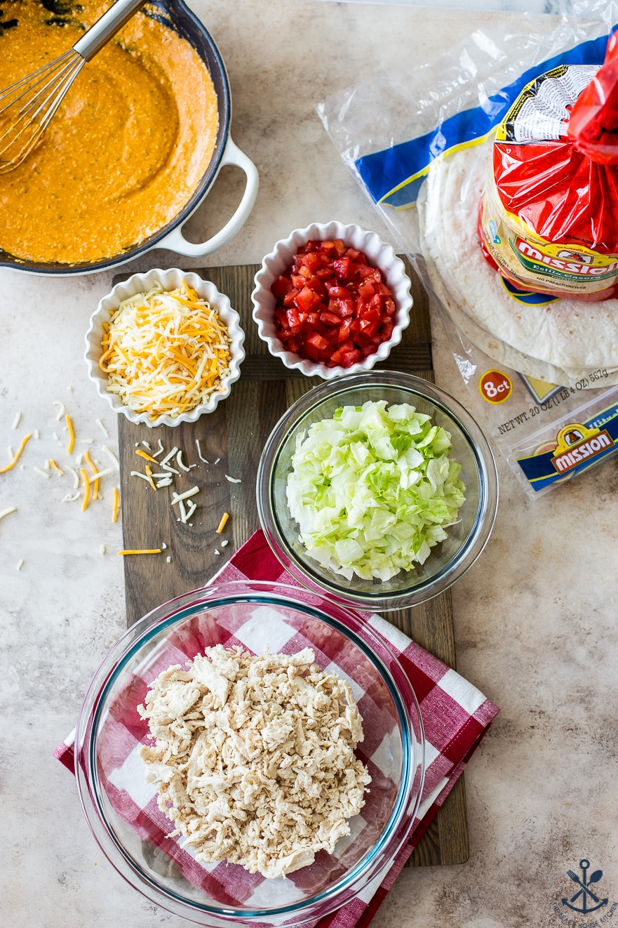 Overhead photo of ingredients for crunchwraps in glass bowls on a wooden board