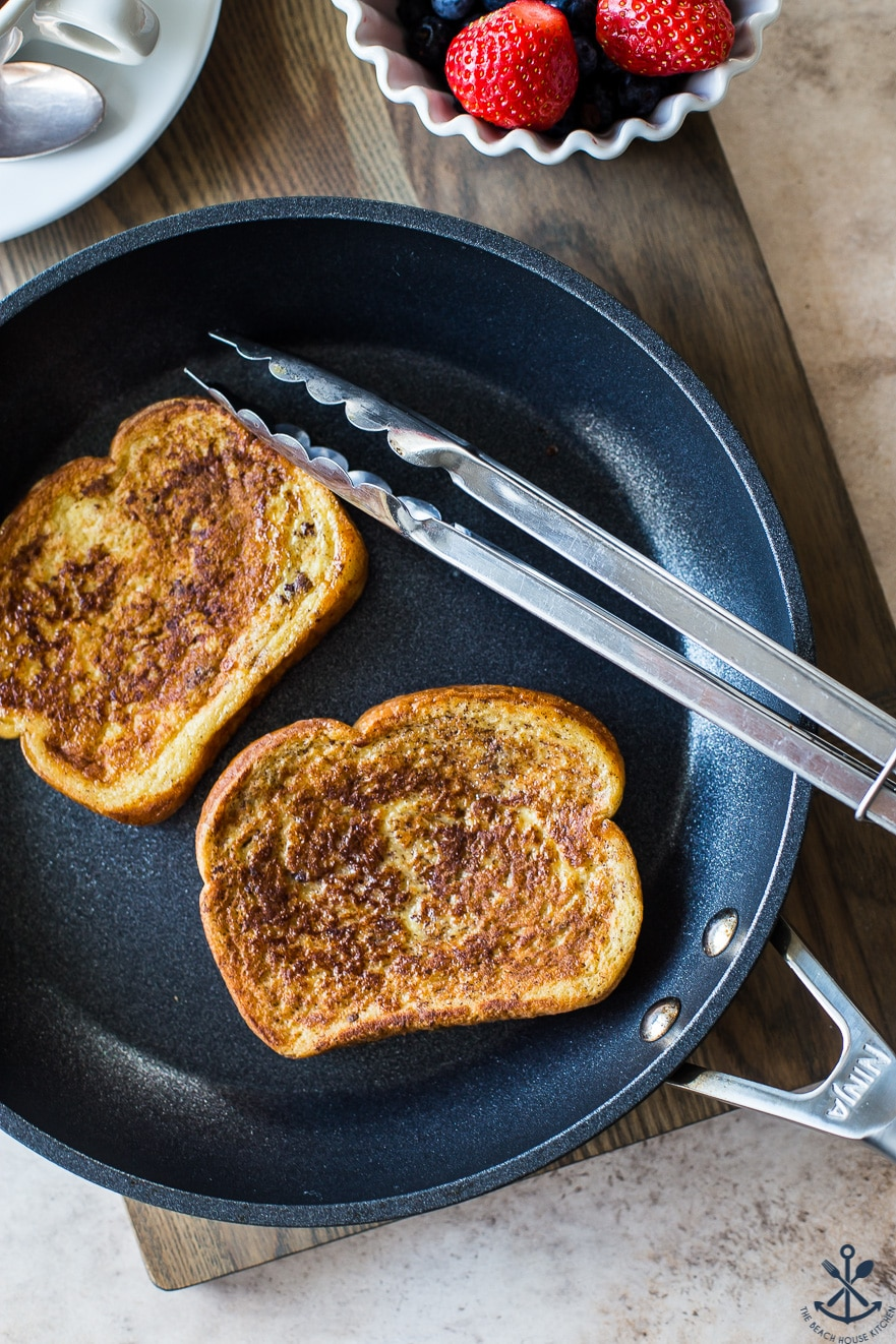 Overhead photo of a skillet with two slices of french toast and a set of silver tongs