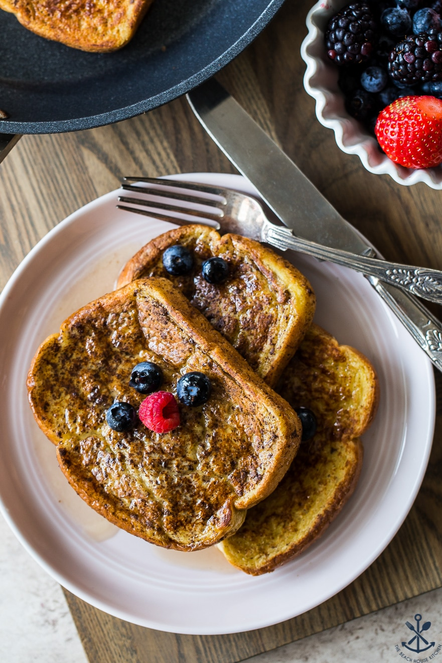 Up close overhead photo of three slices of french toast topped with berries