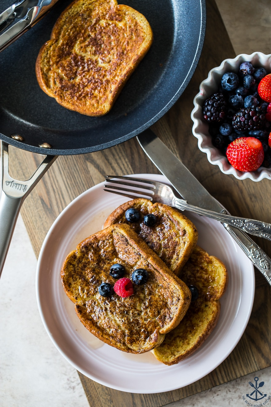 Overhead photo of french toast slices on a plate with berries and a fork and knife