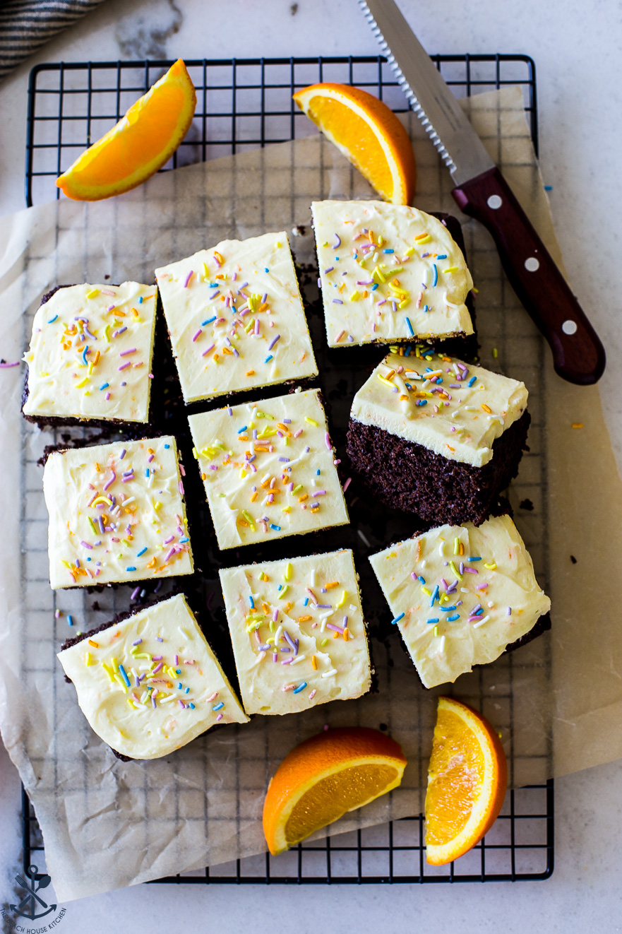 overhead photo of iced chocolate cake surrounded by orange slices and a sharp knife