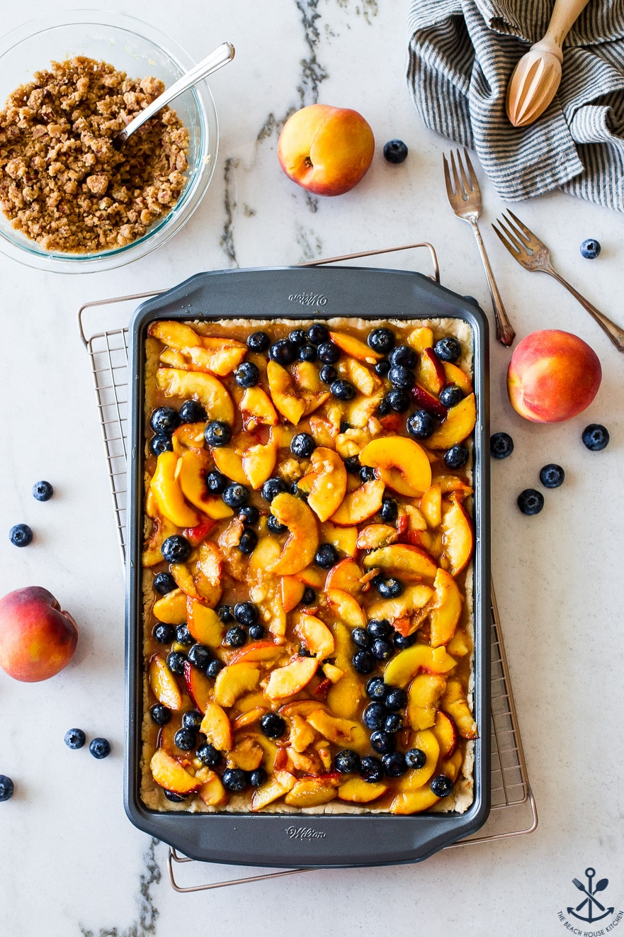 Overhead photo of sheet pan filled with peaches and blueberries
