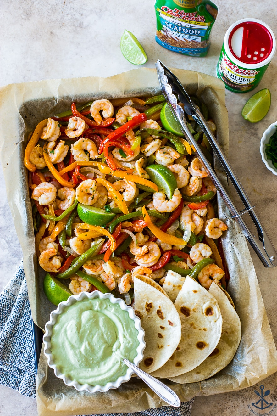 Overhead photo of a sheet pan filled with shrimp and onions and peppers and a bowl of avocado crema
