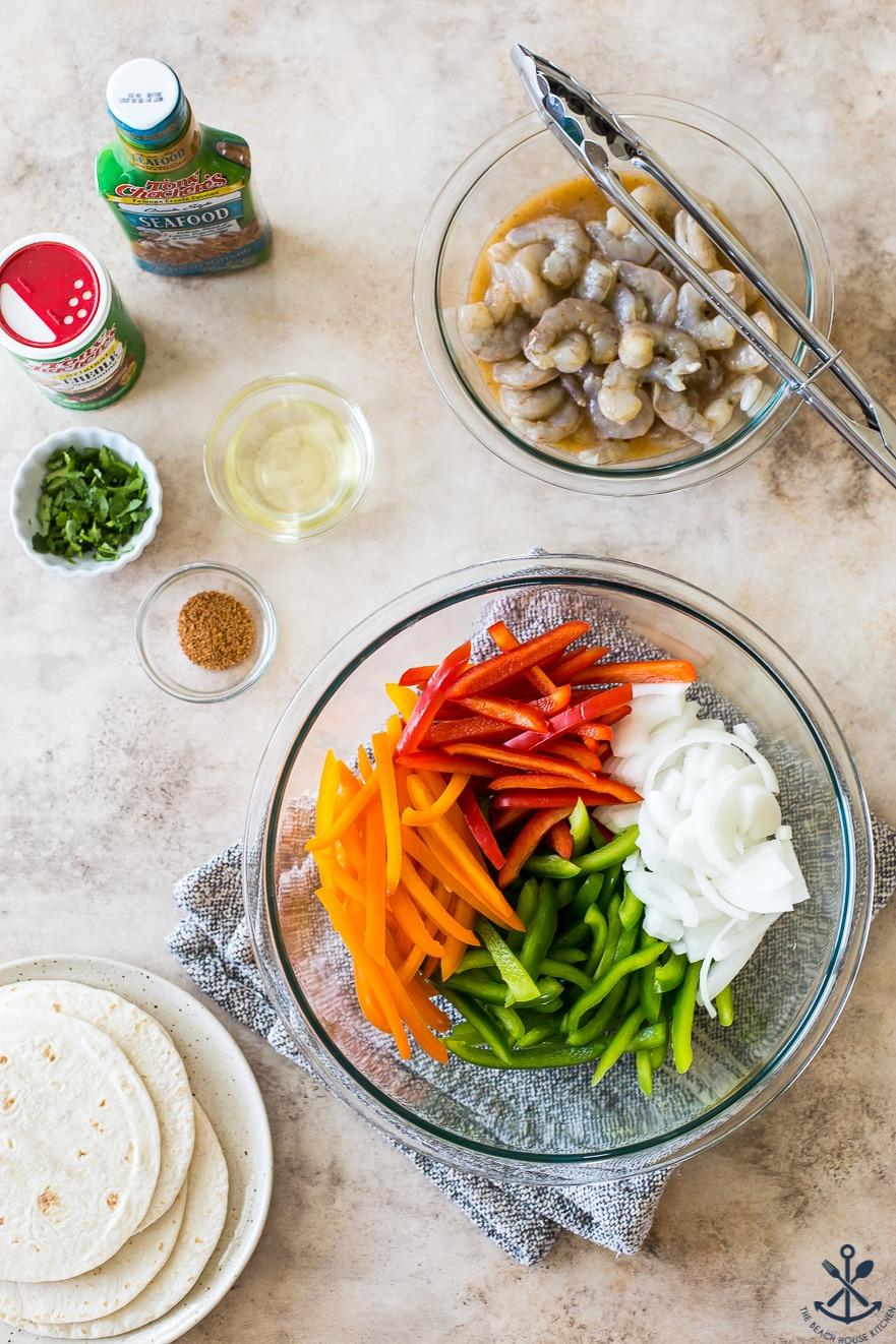 Overhead photo of ingredients for sheet pan shrimp fajitas in bowls