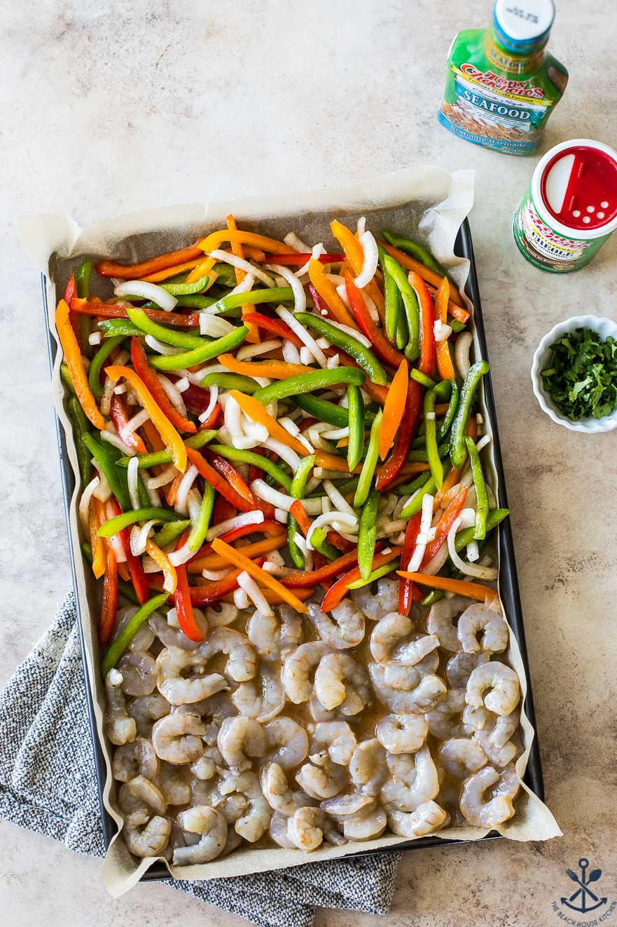 Overhead photo of a sheet pan filled with uncooked shrimp, onions and peppers