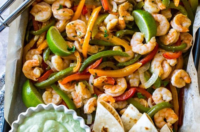 Overhead photo of shrimp and veggies on baking sheet with avocado creama