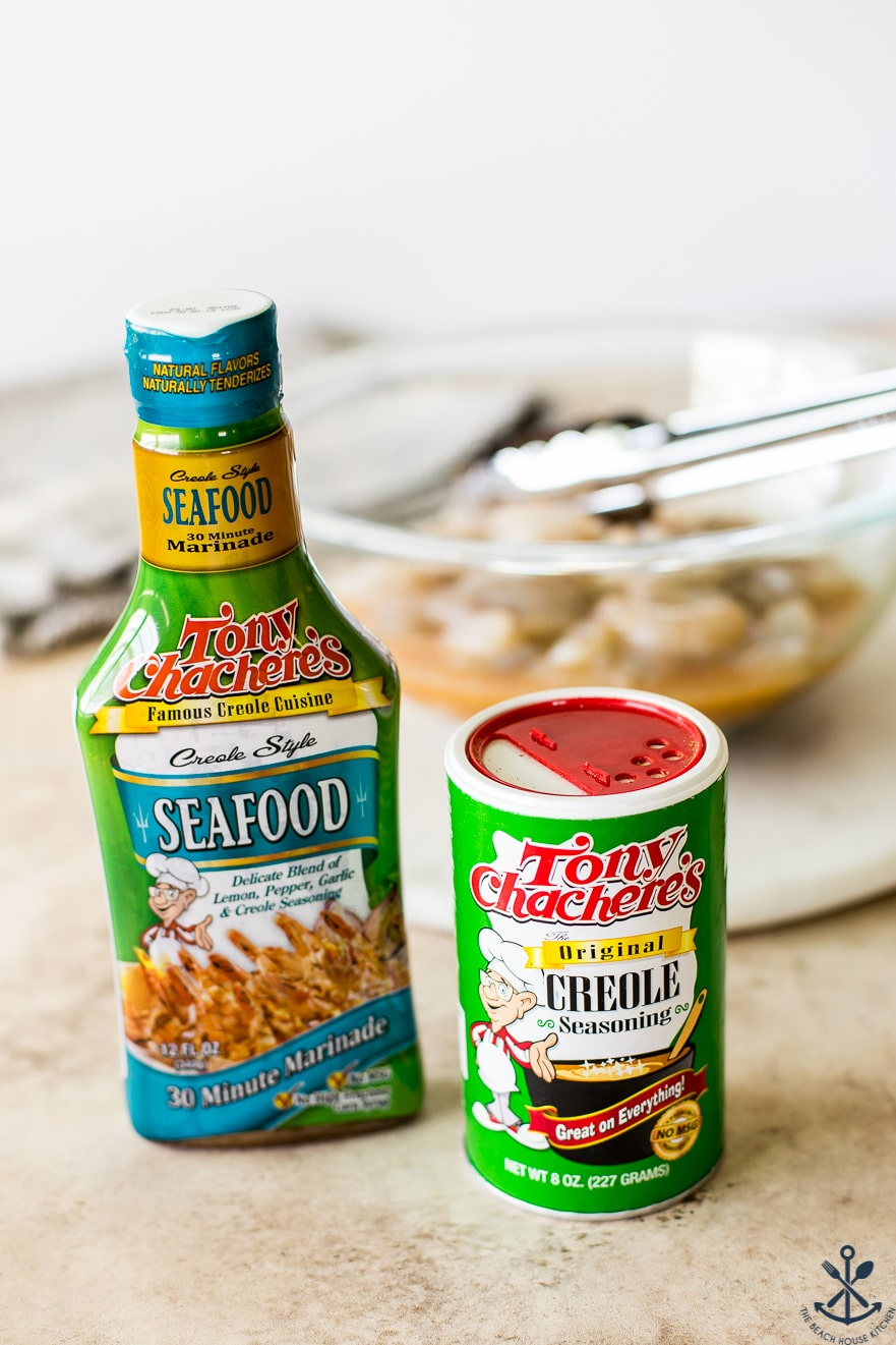 A bottle of Tony Chachere's Seafood Marinade and a can of creole seasoning