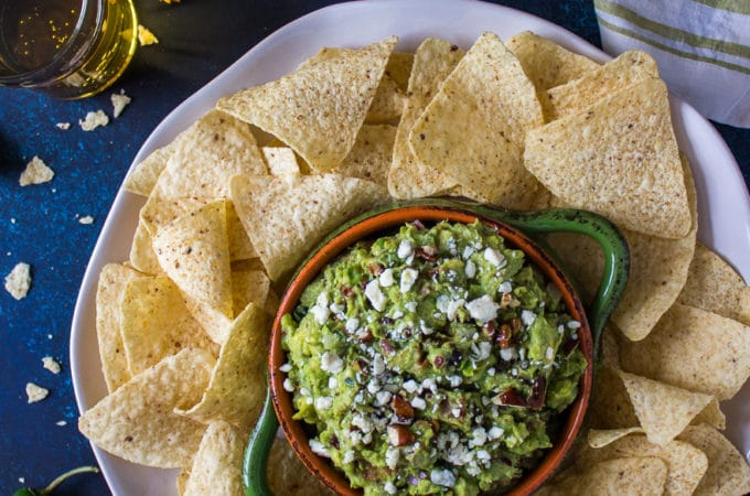 Overhead photo of guacamole in a bowl on a tray with tortillas