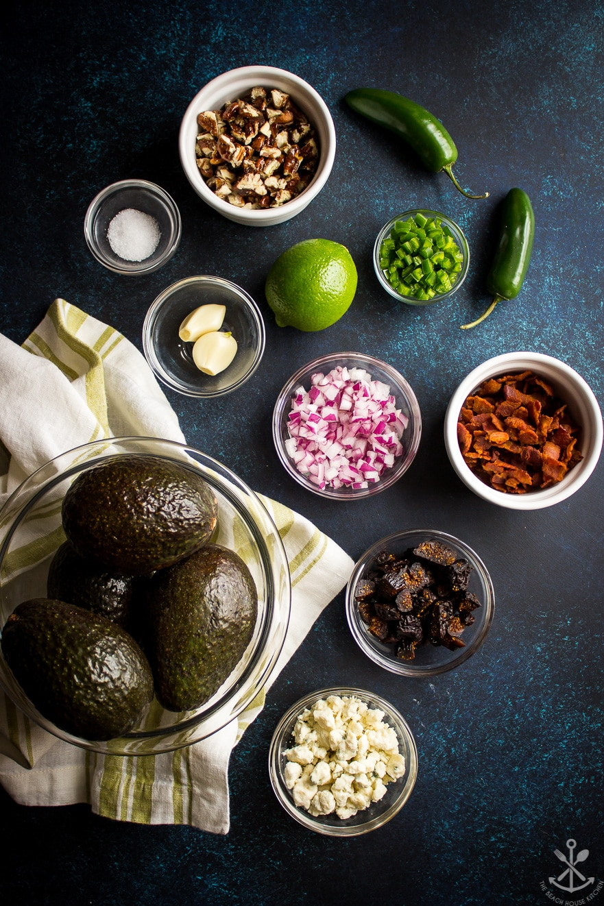 Overhead photo of ingredients for guacamole in bowls on a blue background