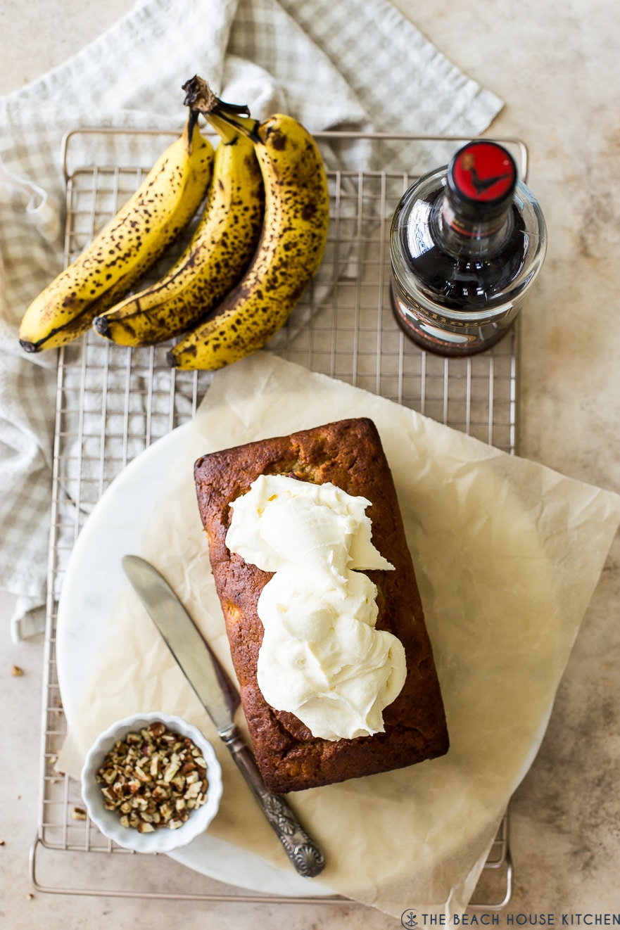 Overhead photo of banana bread topped with cream cheese frosting on a wire rack with bananas and dark rum bottle