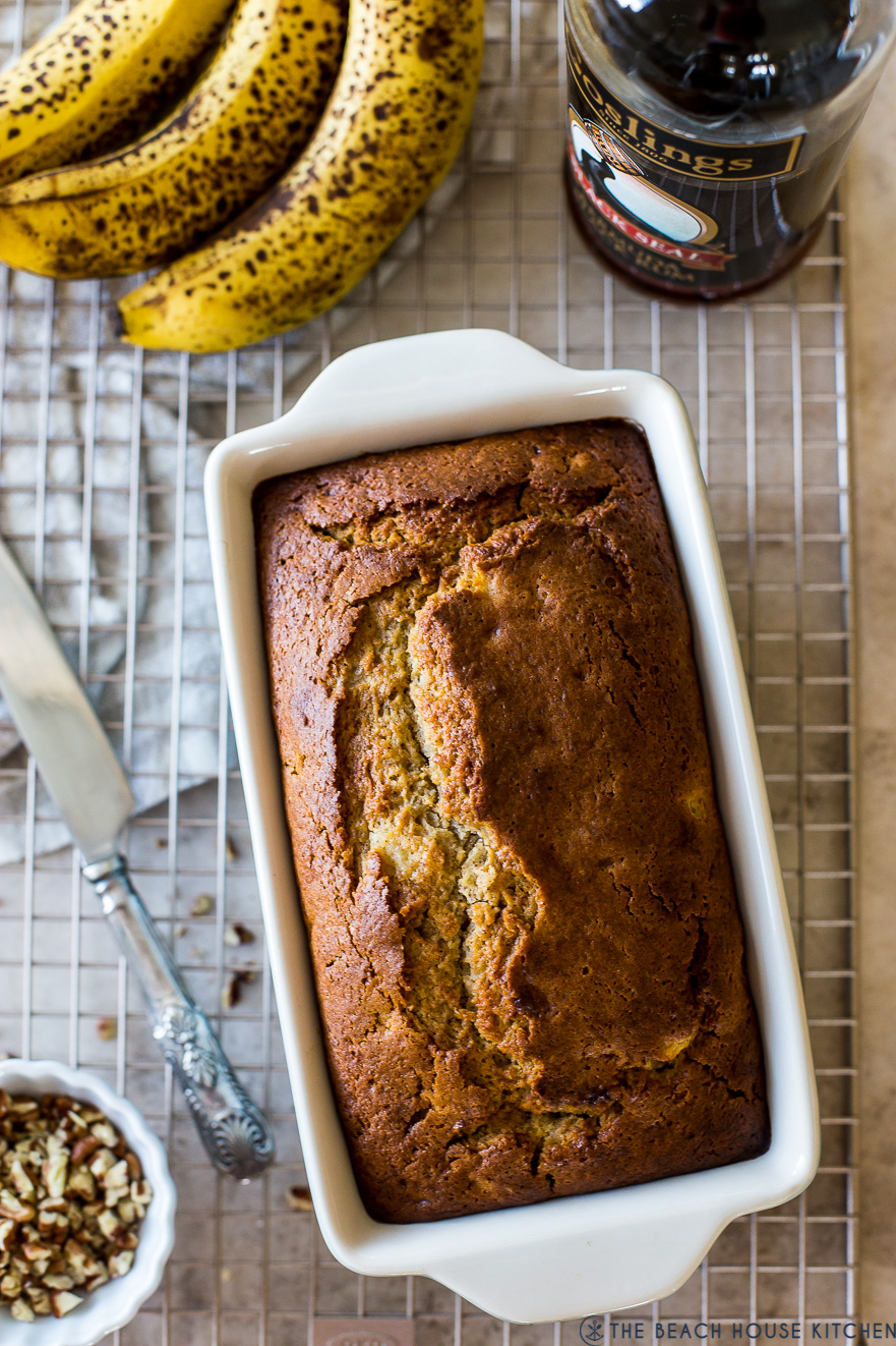 Up close Overhead photo of banana bread on a wire rack with bananas and a bottle of rum