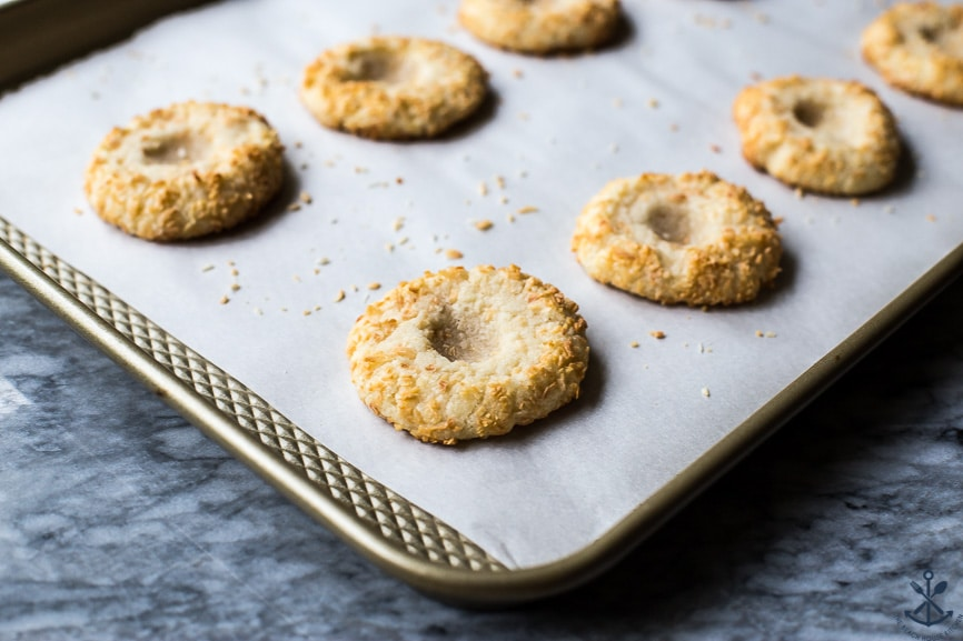 A baking sheet of pre-filled coconut thumbprint cookies