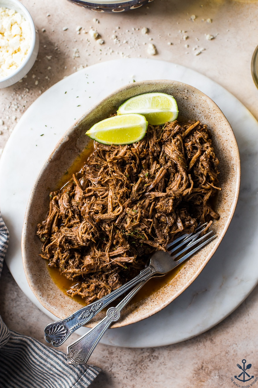 Up close overhead photo of beef barbacoa on an oval plate with limes and two forks