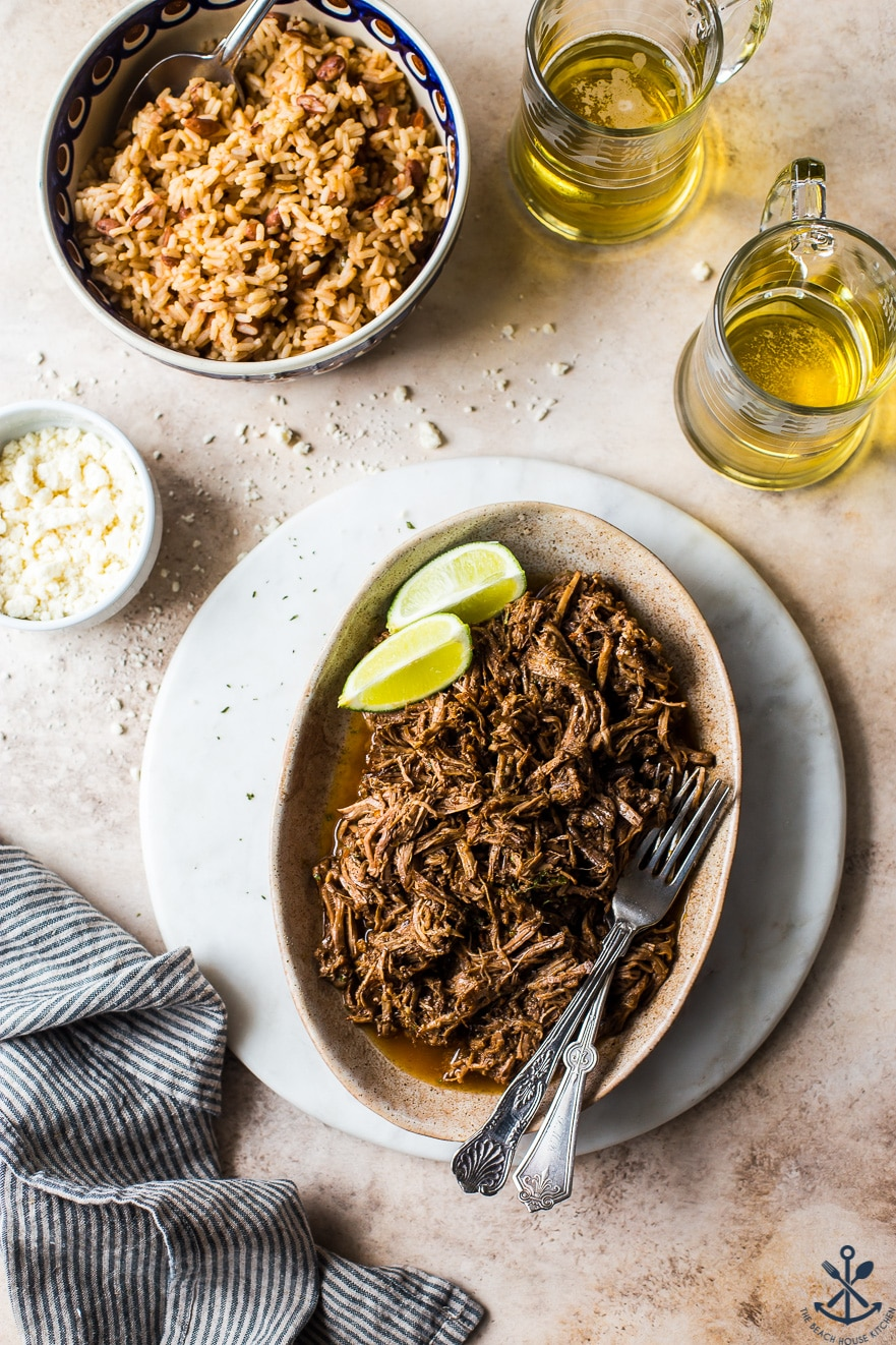 Overhead photo of beef barbacoa on an oval plare with a bowl of rice two mugs of beer