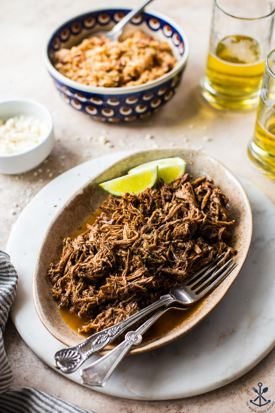 Ovan plate of shredded beef with two lime slices and two forks with a bowl of rice and two glasses of beer in background