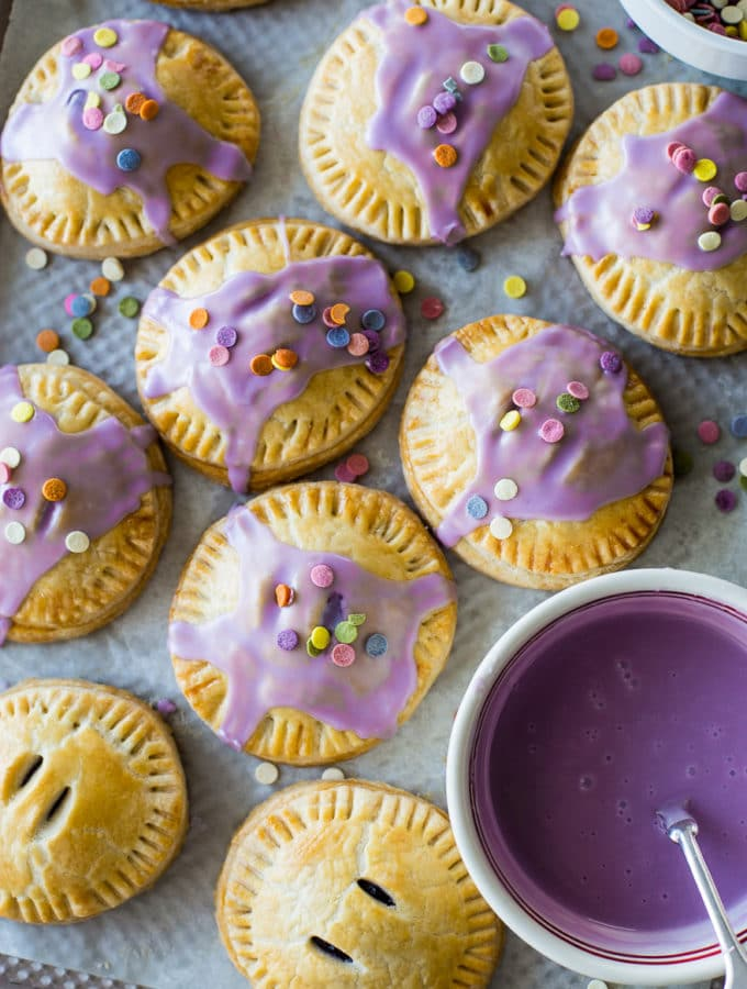 Up close overhead photo of purple Glazed Blueberry Hand Pies with sprinkles