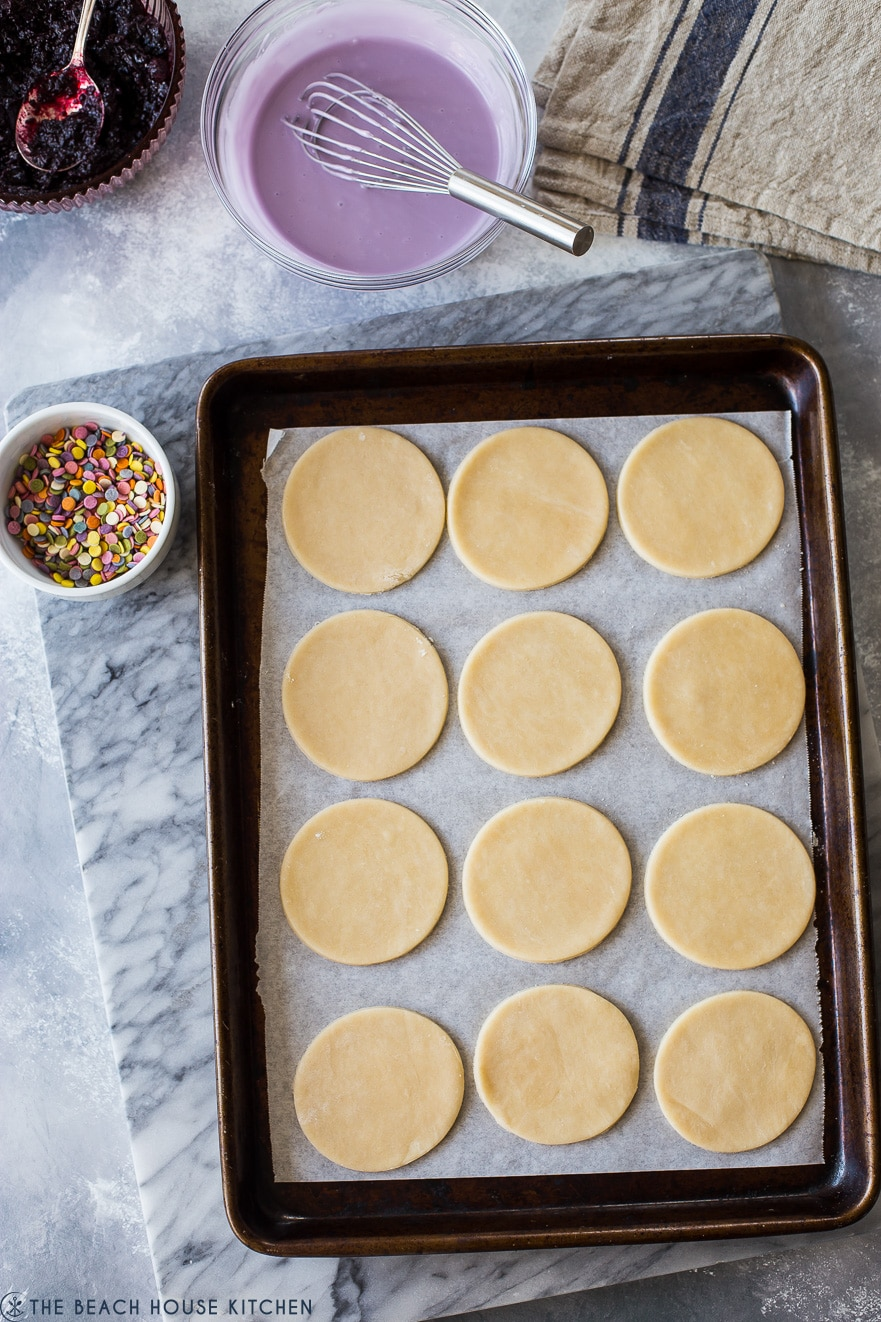 Overhead photo of baking sheet of prebaked round pie dough pieces with a bowl of sprinkles and a bowl of purple glaze