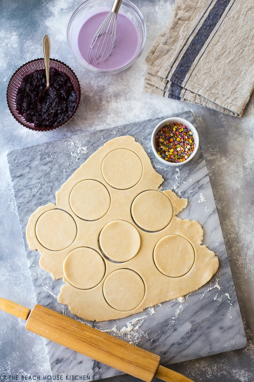 Overhead photo of dough for hand pies on a marble board with a bowl of blueberry jam and a rolling pin