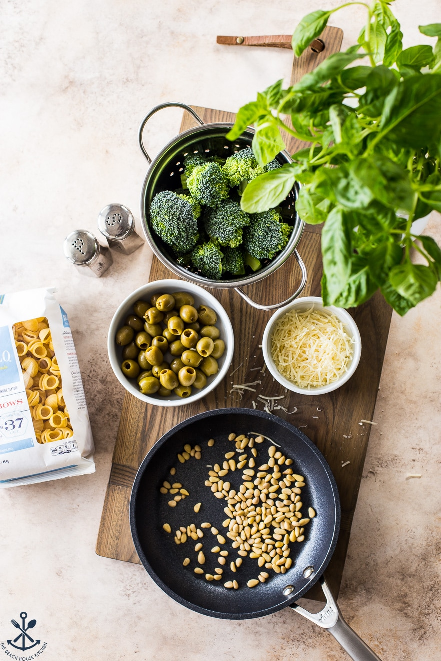 Overhead photo of ingredients for pesto pasta with broccoli, pine nutes, olives and basil