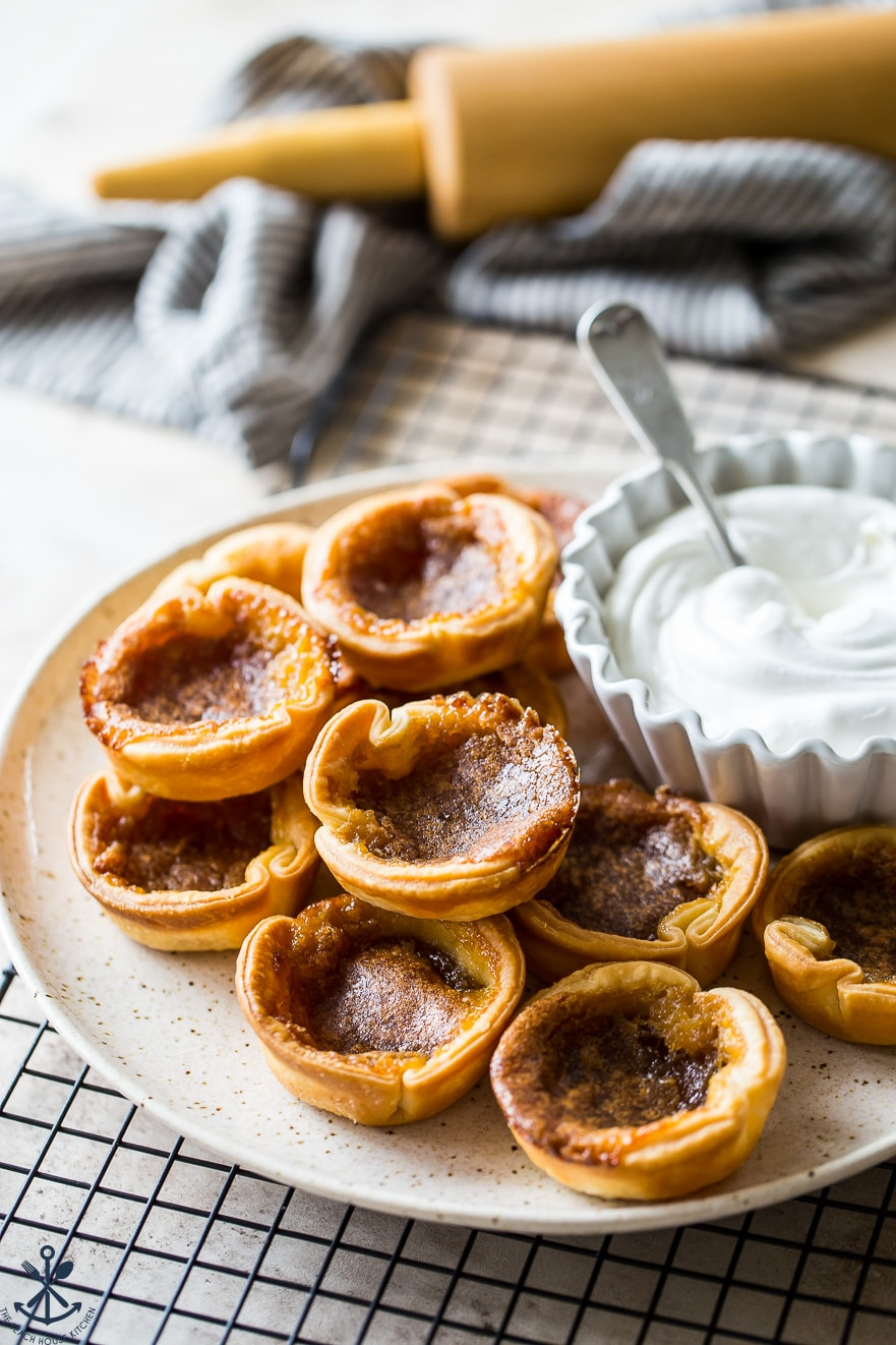 A plate of little butter tarts with a bowl of whipped cream and a rolling pin in the background