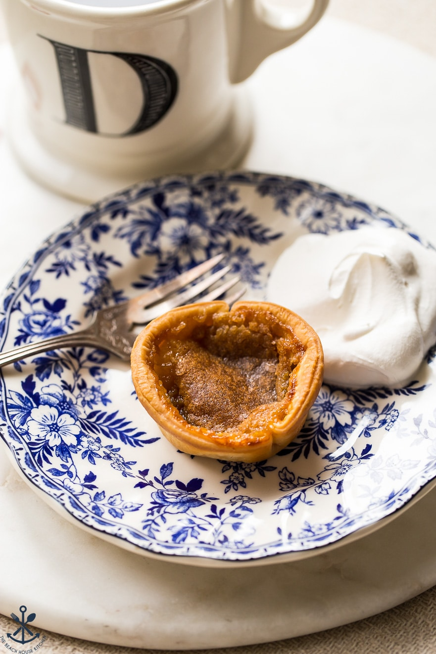 A blue and white plate with a little tart and whipped cream on it