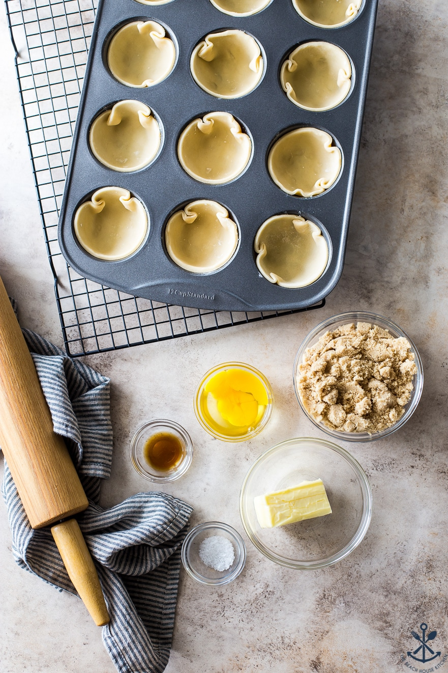 Overhead photo of a muffin tin filled with tart dough and small glass bowls filled with filling ingredients