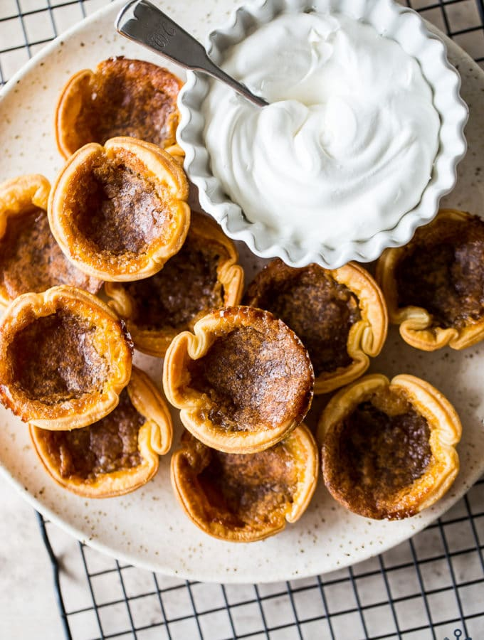 Overhead photo of a plate of Canadian Butter Tarts with a bowl of fresh whipped cream