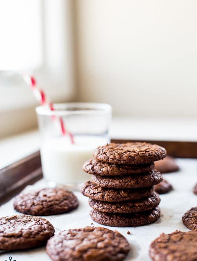 A stack of brownie cookies with a glass of milk in the background