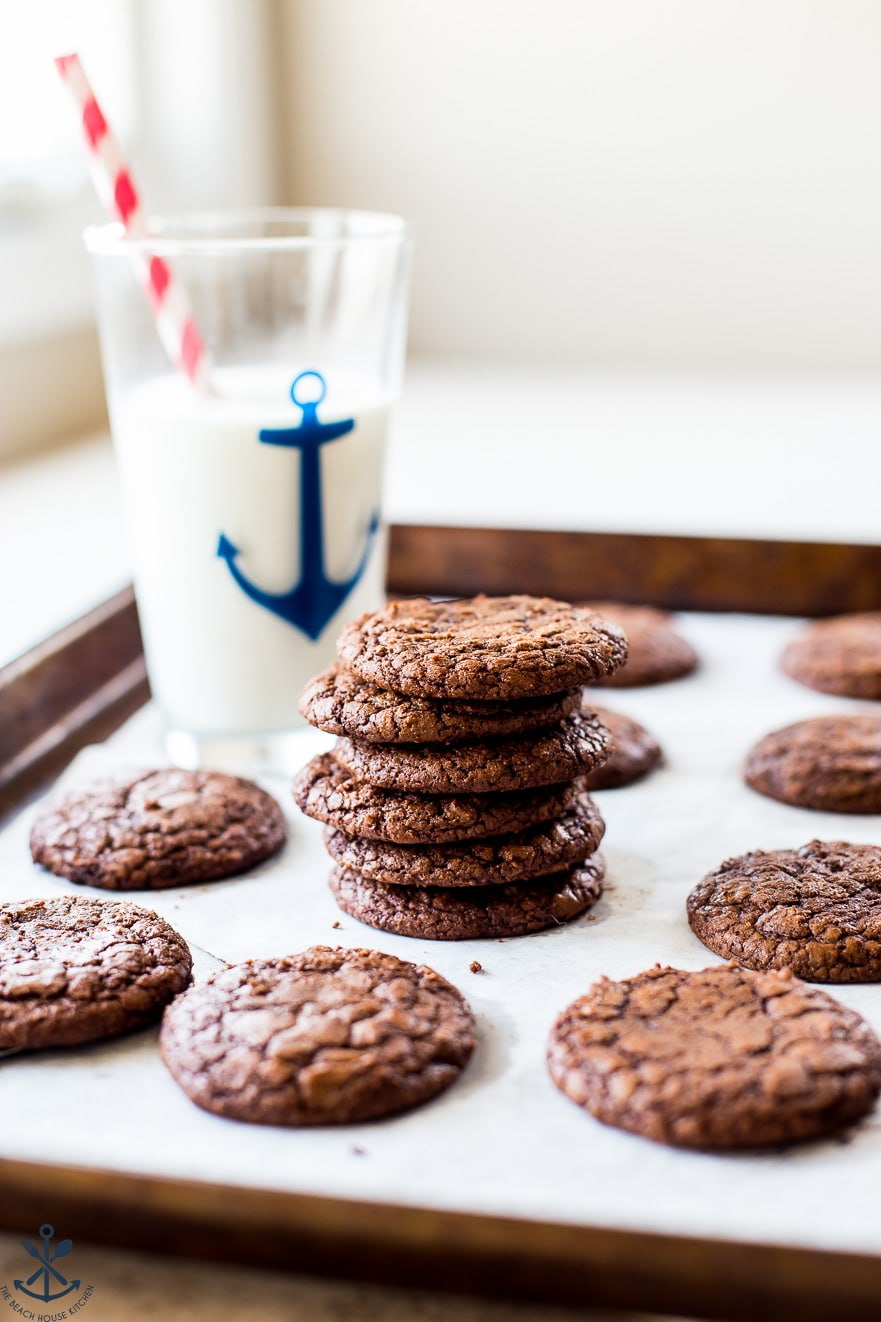 A stack of brownie cookies with a tall glass of milk behind it