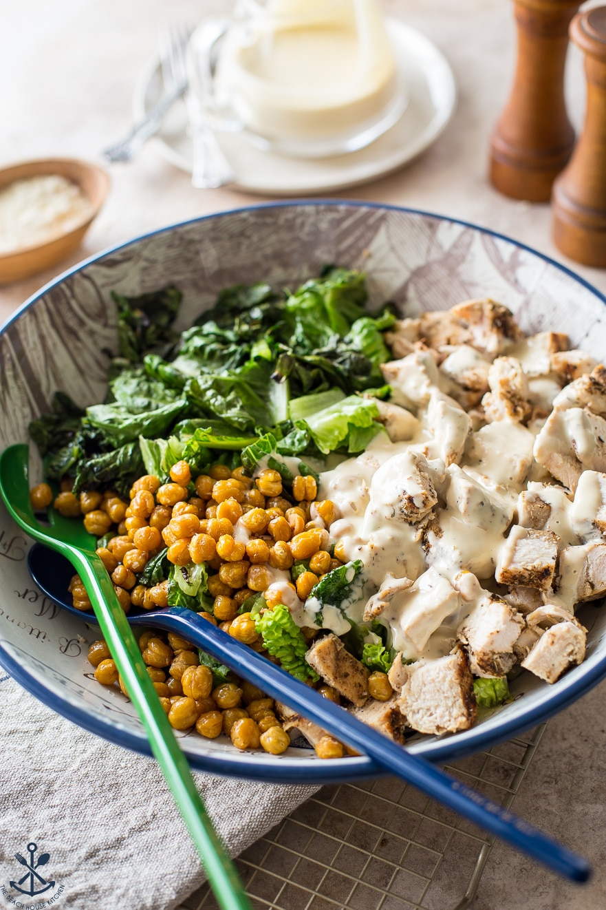 A bowl filled with romaine, roasted chick peas and chunks of chicken covered in Caesar dressing