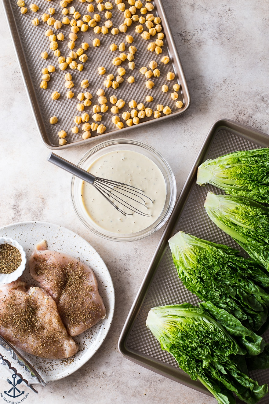 Overhead phot of sheet pan of chick peas, bowl of dressing with a whisk, plate of chicken with blackening seasoning and sheet pan with halved heads of romaine lettuce