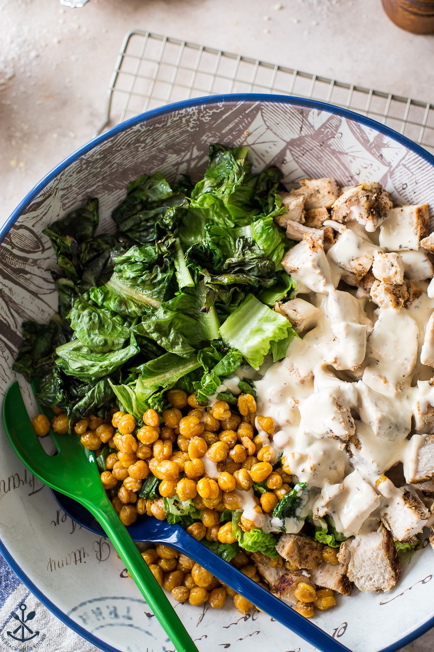 Overhead photo of a bowl filled with romaine, roasted chick peas and chunks of chicken covered in Caesar dressing